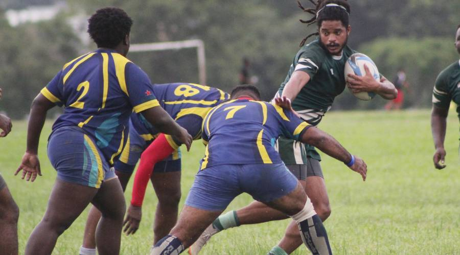 Harvard's Asan Lewis tries to evade several tackles from Royalians players headed by Akel Welsh during their TTRFU Championship Division League match on Royalians Grounds at the Queen's Park Savannah, Port-of-Spain, on Saturday. Harvard won 22-15.