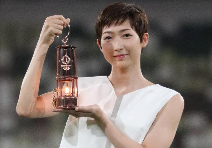THE COUNTDOWN STARTS: Japanese swimmer Rikako Ikee holds a lantern containing the Olympic flame during an event yesterday marking one year until the postponed Tokyo 2020 Olympic and Paralympic Games, at the National Stadium in Tokyo.  —Photo: AFP